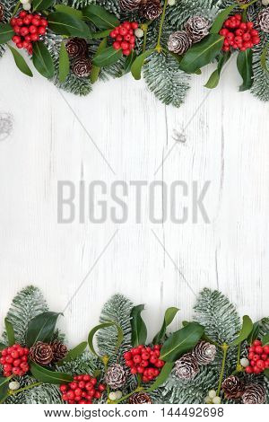 Winter and christmas abstract background border with traditional flora of holly, mistletoe, snow covered fir and pine cones over distressed white wood.
