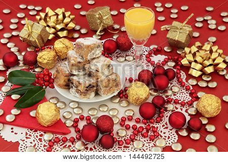 Christmas still life with egg nog, stollen cake bites, gold foil wrapped chocolates, holly and bauble decorations on a red background.