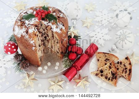 Chocolate panettone christmas cake and slice with holly berries, cracker, red, silver, gold and white snowflake, round and star shaped bauble decorations and fly agaric mushroom ornament.