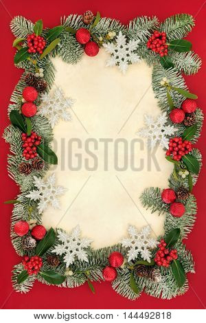 Christmas abstract background border with glitter snowflake and red bauble decorations,  holly, mistletoe and snow covered cedar cypress on old parchment paper.