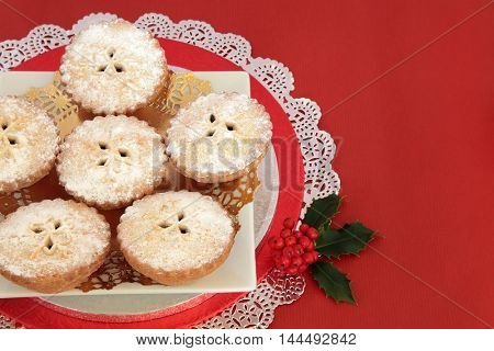 Mince pie christmas cakes with holly over red background with copy space.