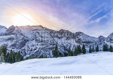 Snowy mountain peaks - Lovely winter scenery with the rocky peaks of the Austrian Alps mountains their evergreen fir forests and the pastures covered in snow everything warmed up by a colorful sun.