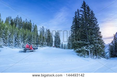 Snowy roads through alpine forest, in Austria - Winter scenery with lots of snow over the forestry roads in the Austrian Alps mountains and two snow groomer vehicles clearing the way.