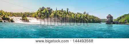 The Rhine Fall on a sunny day - Panorama with the Rhienfall the Laufen castle and Worth Castle while boats navigate the blue waters of the river in Switzerland.