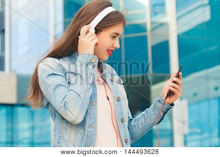 Beautiful girl listening music in headphones and smiling looking at the phone .The concept of good music and fun