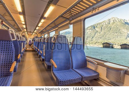 Train chairs and mountain view through the window - Image with the interior of a german border train with comfortable modern chairs and a mountain landscape viewed through the window.