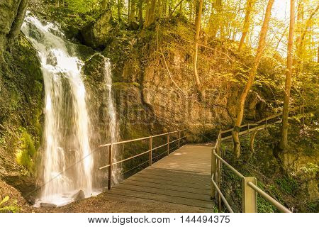 Wooden bridge over a small waterfall in the forest - Idyllic scenery of a small waterfall and a bridge that crosses it in the forests of the Swiss Alps from Walensee St Gallen Canton Switzerland.