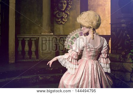 Victorian lady. Young woman in eighteenth century image posing in vintage exterior