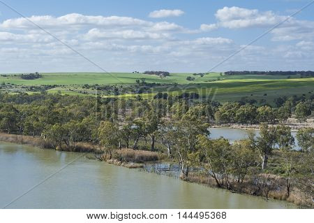 Blue cloudy skies over the Murray River lined with gum trees and tried brush with filtered sun through the clouds on green fields in the background at Young Husband South Australia.
