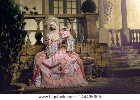 Victorian lady. Young woman in eighteenth century image posing in vintage interior