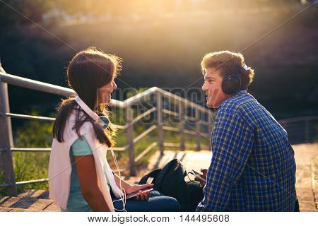 Two best friends girl and boy sit in the stair outdoor