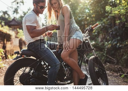 Couple Outside On Bike Looking At Mobile Phone