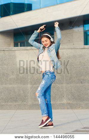 Beautiful girl in denim suit dancing and listening to music on headphones . She was overwhelmed with emotions .The concept of good music and fun