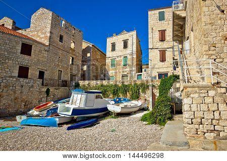 Old waterfront of Komiza stone architecture and boats on beach Island of Vis Dalmatia Croatia
