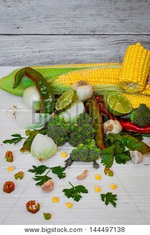 set of vegetables on white wooden background with tomatoespepperscornonionsparsleylime garlic
