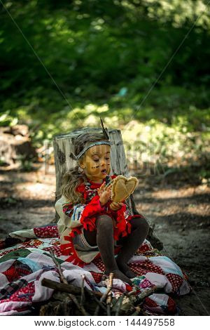 beautiful little girl playing outdoors in Indians eating an Apple sitting on a stump
