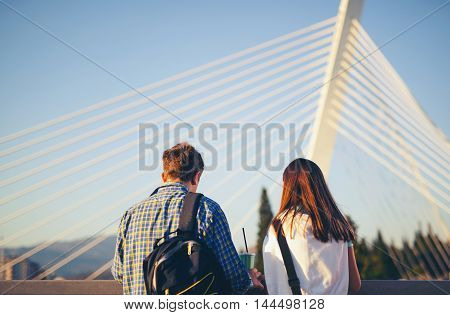 Two teenagers friends standing on the bridge and watch the river