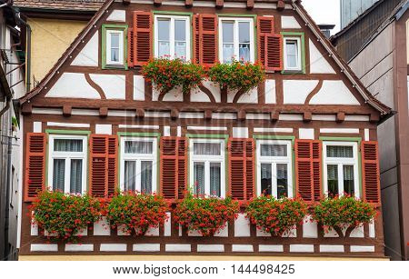 Wall of old house with potted flowers on windows, historic old German town Calw, autumn city landscape with flowers