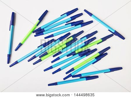 ballpoint pens of different colors on a white background.