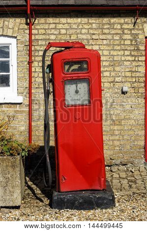 HAINTON ENGLAND - AUGUST 26: Old fashioned vintage red petrol (gas) pump next to the Heneage Arms pub. In Hainton Lincolnshire England. On 26th August 2016.