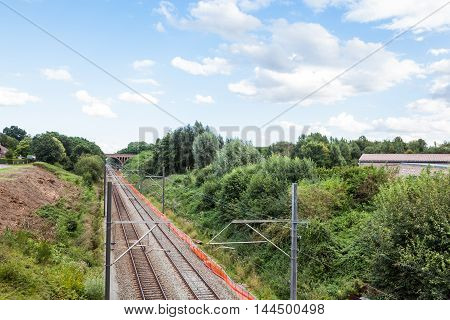 train tracks disappearing into the horizon with cloudy skies