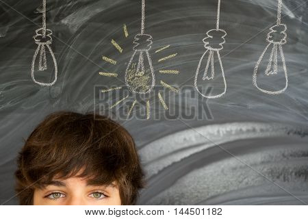 Eyes of teenager boy against getting an idea blackboard background