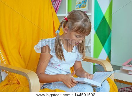 Cute little girl with pigtails sitting in a chair and reading a book