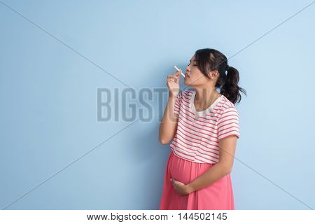 unhealthy Asian pregnant woman smoking