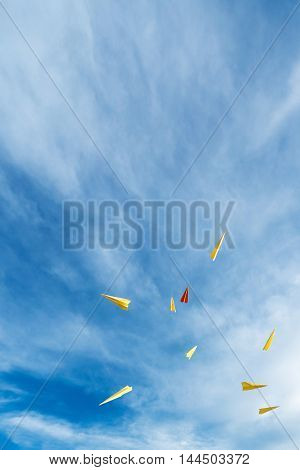 yellow and orange aircraft rocket paper floating in beautiful blue sky. Text space.