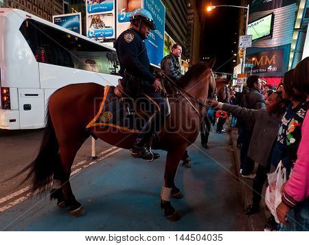 New York USA - November 20 2011: Two Police Officers riding horses at Broadway in Times Square New York City USA. People walking towards police horses and talk to officer.