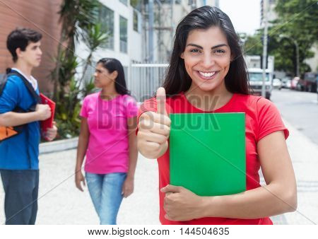 Happy latin female student in red shirt showing thumb