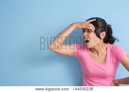 Asian young woman got a headache, closeup portrait with copyspace on wall.