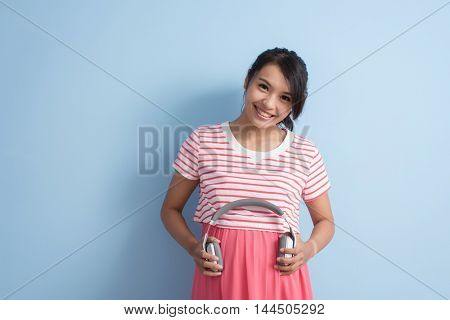 Asian young pregnant put earphones on her belly. Concept of prenatal education.