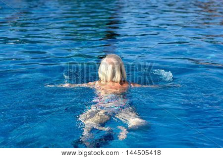 Active Senior Woman Swimming In A Pool