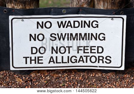 White warning sign with black letters. No Wading. No Swimming. Do not feed the Alligators. Seen in Florida.