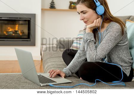 Beautiful woman working at home with a laptop while listen music