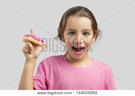 Studio portrait of a beautiful girl with a donut on her finger