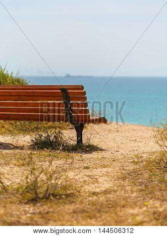 wooden bench close-up on a sandy sea shore
