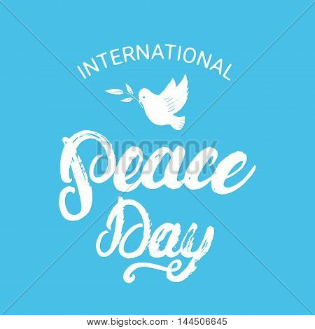 International Peace Day hand written calligraphy lettering poster or card with hand drawn dove and olive branch on blue background. Brush ink texture. Vector illustration.