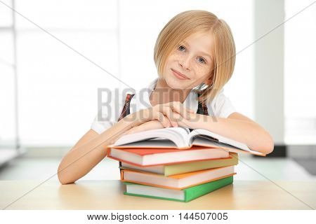 Smiling girl with many books at school