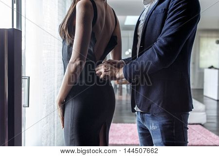 Macho man dressing woman into cocktail dress indoor closeup
