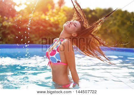 Caucasian girl splashing water with hair in pool sunset