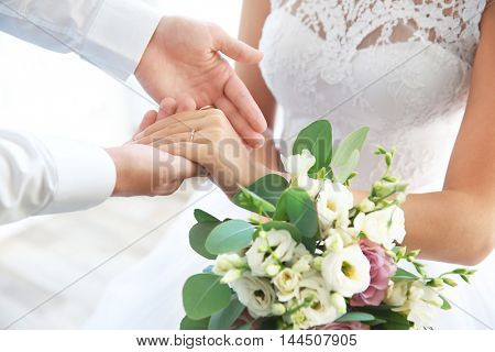 Groom and bride holding hands closeup
