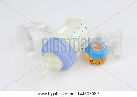 Feeding bottle with baby milk formula and bottle with medicine on white background