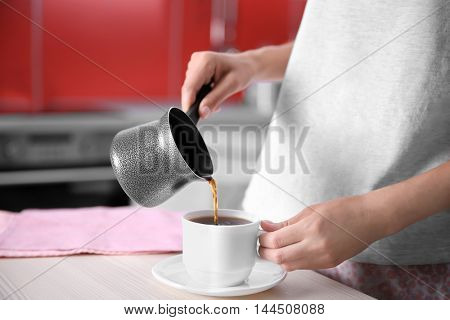 Woman pouring coffee in kitchen