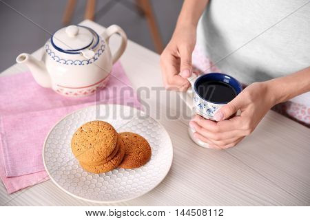 Breakfast concept. Woman with cup of tea in kitchen