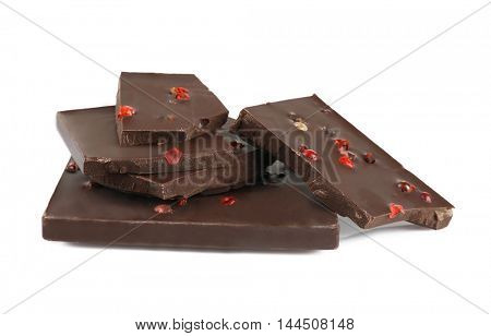 Pile of dark chocolate tiles with peppercorns isolated on white