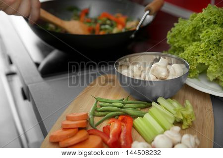 Fresh sliced vegetables on wooden cutting board in kitchen