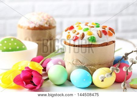 Easter Eggs With Cake On A White Wooden Table