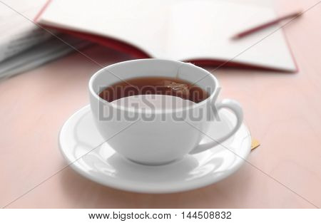 Cup of tea with notebook on table